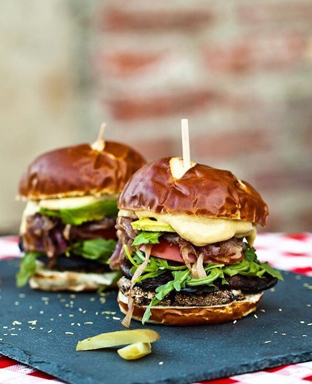 Smoky Portobello Black Bean Burgers with Roasted Garlic Aioli by @carrotsandflowers Prep Time30minutes Cook Time1 hour, 10minutes Servings6burgers Ingredients •2cans black beansdrained •1/2cuprolled oats •1/2cupbread crumbs •1tspliquid smoke •1tspcumin •1 1/4tspsea salt •1 1/2tspchili powder •6portobello mushroom caps, spores removed •6clovesgarlic, minced •1/4cup+ 2 tbsp soy sauce •1/4cup+ 2 tbsp balsamic vinegar •2tbspolive oil, divided •1red onion, thinly sliced •6vegan burger buns (we love pretzel buns!) Roasted Garlic Aioli •2headsgarlic •1cupraw cashews •4tbsp + 1 tspgrapeseed oil •1/2cuphot water •2tbspnutritional yeast •2tsplemon juice •1/2tspsalt •1/2tsppepper Instructions 1) Trim the ends of the heads of garlic, being sure to cut the tip off every clove. Drizzle 1/2 teaspoon grapeseed oil on the ends of each head of garlic. Wrap the garlic in foil and bake for 40 minutes. Meanwhile, boil the cashews in a small pan of water for 10 minutes to soften, then drain. Set the cashews and roasted garlic aside to make your aioli when the black bean patties are in the oven. 2) In a medium bowl, mash the black beans until they are about half mashed, half whole. Stir in the liquid smoke and spices. Mix well. Add the oats and mix with your hands until evenly combined. Divide the black bean mixture into six even balls, then shape the balls into patties. 3) Pour the bread crumbs into a shallow dish and evenly coat each black bean patty in bread crumbs. Place in the freezer for twenty minutes to firm up. Meanwhile, combine the garlic, soy sauce, balsamic vinegar, and olive oil in a small bowl. Stir well. Place the portobello mushroom caps in two oiled baking pans. Pour the balsamic soy marinade over the portobellos, evenly distributing the marinade between the 6 caps. Set aside for 15 minutes and preheat the oven to 350F. 4) Heat 1 tablespoon olive oil over medium heat. Add the red onion and stir well. Cook for 1-2 minutes, then cover and reduce heat to low. Allow the onio