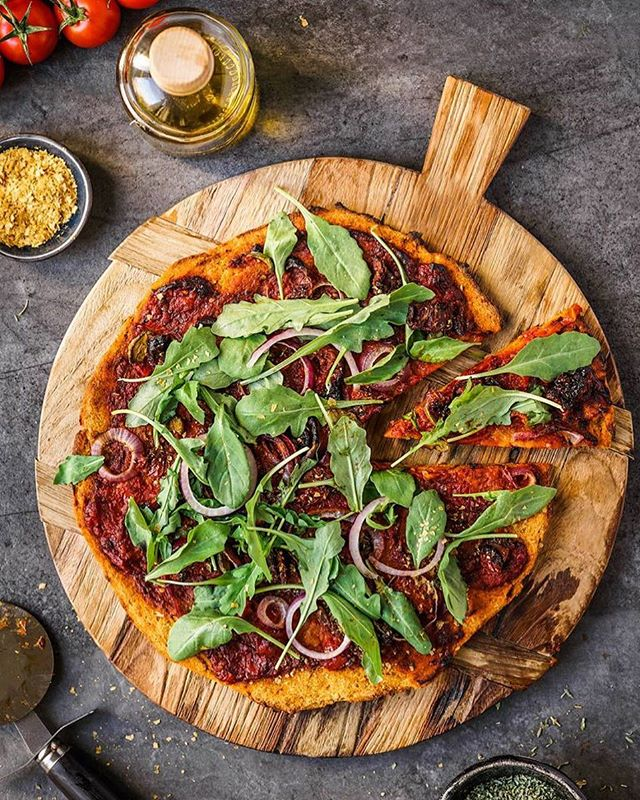 Butternut squash pizza by @aboutthatfood ️ . Recipe as posted on aboutthatfood.com: . Makes 1 large pizza. Ingredients for the base: 3 cups pumpkin steamed or roasted 1/3 cup oat milk 1 tsp tomato paste 1 tbsp olive oil 1 tbsp thyme 1 tsp salt 1 1/2 Cups flour for the toppings: 1 cup cherry tomatoes 1 tbsp olive oil 2 tbsp tomato paste 1/2 tbsp dried basil 1/2 tbsp dried oregano 1/2 tsp salt 4-5 sundried tomatoes 4-5 Kalamata olives a few slices of red onion a small handful of arugula a few tsp of nutritional yeast Method: Preheat the oven to 220°C. Cut your butternut squash into cubes and roast in the oven or steam until very soft. Place all of the ingredients for the base, except for the flour, into a food processor and blend until very smooth. Next add the flour bit by bit while the food processor is running. The batter will turn into a sticky dough. With the help of the back of a spoon spread the dough out thinly on a sheet of baking paper. For the tomato sauce cut the cherry tomatoes in half and add into a small saucepan with the oil, tomato paste basil, oregano and salt and cook with the lid on on medium heat until the tomatoes have dissolved and everything has incorporated into a nice sauce. Stir every now and then. Once the tomato sauce is done spread on top of the pizza base, top with olives, onions and sun dried tomatoes. Drizzle some oil on top if you like and place into the oven for about 15 mins. Once its out of the oven top with the arugula and nutritional yeast and serve.